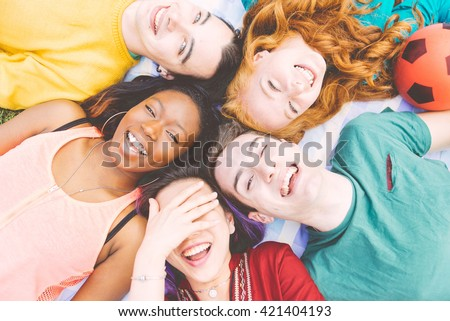 Group of four friends laughing out loud outdoor, sharing good and positive mood. - stock photo
