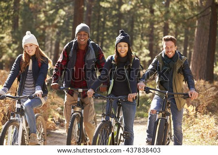 Group of four friends on bikes in a forest looking to camera - stock photo