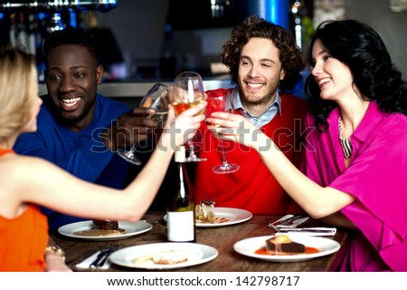 Group of four friends raising a toast - stock photo