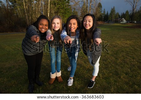 Group of four girls pointing fingers and smiling - stock photo
