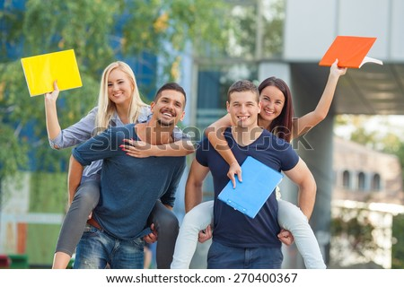 Group of four happy students having fun in campus - stock photo