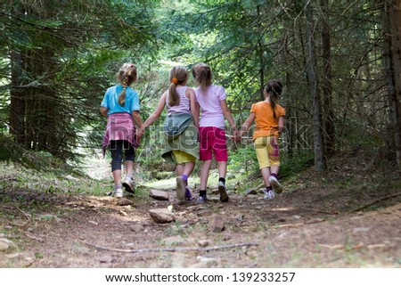 Group of four little girls running in the forest - stock photo