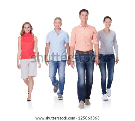 Group of four people walking towards camera. Isolated on white - stock photo