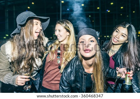 Group of four pretty girls having party, smoking and drinking alcohol - Best friends clubbing in the night, frontal flash to give realism to the scene - stock photo