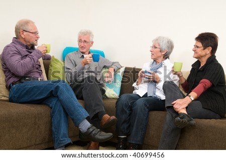 Group of four seniors drinking coffee, chatting and having a great family time together. - stock photo