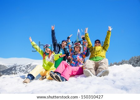 Group of four snowboarders friends sitting on the snow in the - stock photo