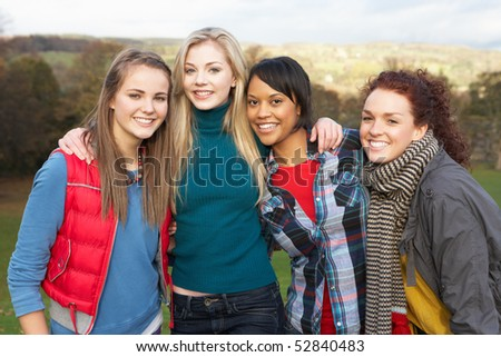 Group Of Four Teenage Female Friends In Autumn Landscape - stock photo