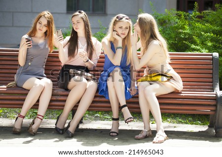Group Of Four Teenage Girls Sitting On Bench In summer Park  - stock photo