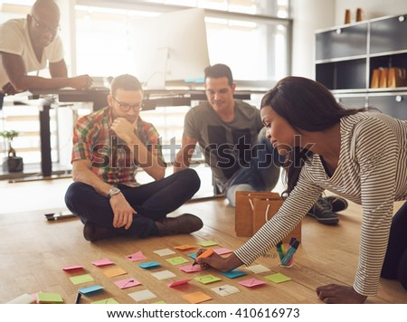 Group of four workers in meeting while sitting around various colored sticky notes on hardwood floor in small office - stock photo