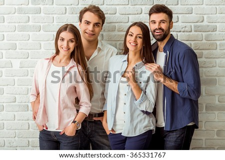 Group of four young beautiful people in everyday clothes,  posing in the studio, smiling, looking at the camera, against a brick wall - stock photo