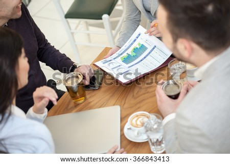 group of four young business people discussing an interesting idea in the cafe - stock photo