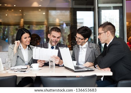 Group of four young business people gathered together at a table discussing an interesting idea in the cafe - stock photo