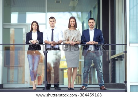 Group of four young business people on a coffee break in front of the office. They are leaning on the railing of the balcony and looking at camera. - stock photo