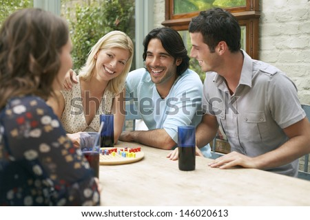 Group of four young people sitting at verandah table - stock photo
