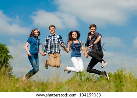 Group of Four Young people two girls & two boys happy smiling in joyful fun jump outdoors in bright sunny day of spring or summer with green field of park or garden and beautiful sky on the background - stock photo