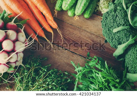 Group of fresh vegetables and herbs on wooden background. Toned image - stock photo