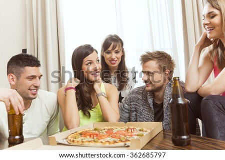 Group of friend having beer and pizza at home - stock photo