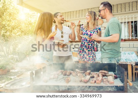 Group of friend having lunch in the backyard. making barbecue outdoor with different kind of meat and vegetables - stock photo