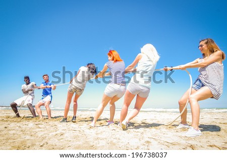 Group of friend playing at tug of war - men against women - stock photo