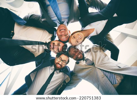 Group of friendly businesspeople in suits looking at camera while standing head to head, below view - stock photo