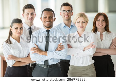Group of friendly businesspeople in suits standing at office. - stock photo