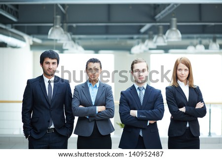 Group of friendly businesspeople in suits standing in line - stock photo