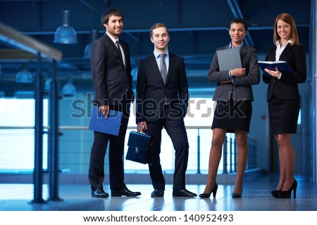 Group of friendly businesspeople in suits standing in line in office building - stock photo