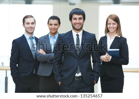 Group of friendly businesspeople with male leader in front - stock photo
