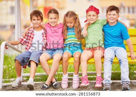 Group of friendly kids sitting on bench outside - stock photo