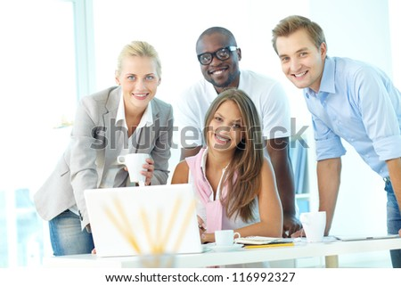 Group of friendly students or businesspeople looking at camera at workplace - stock photo