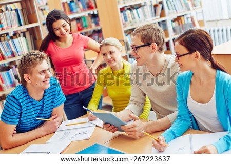 Group of friendly students sitting in college library and communicating - stock photo