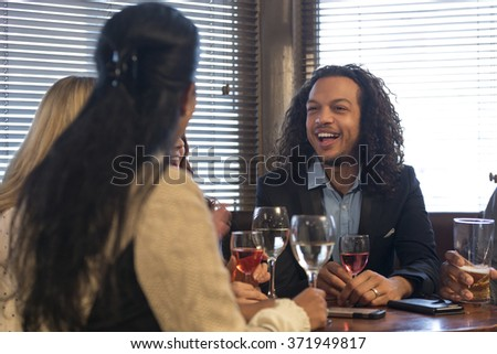 group of friends are drinking wine and beer, and talking in a bar. - stock photo