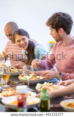 Group of friends are sat down to dinner. They are all laughing and smiling. - stock photo