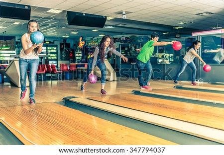 Group of friends at bowling - Young people having fun at bowling, four players throwing balls on the bowling track - stock photo