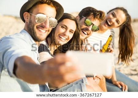 Group of friends at the beach making a selfie together - stock photo
