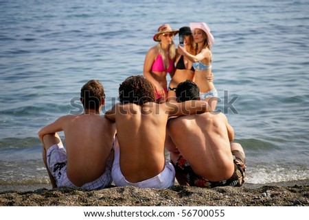 Group of friends at the beach taking photos with a mobile phone - stock photo