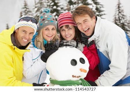 Group Of Friends Building Snowman On Ski Holiday In Mountains - stock photo