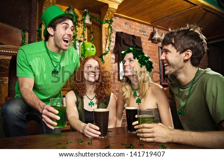 Group of friends celebrating St. Patrick's Day at a pub. - stock photo