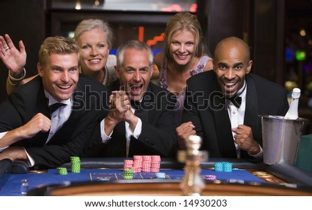Group of friends celebrating win at roulette table in casino - stock photo