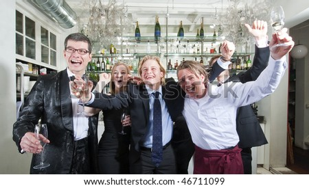 Group of friends cheering in a restaurant bar - stock photo