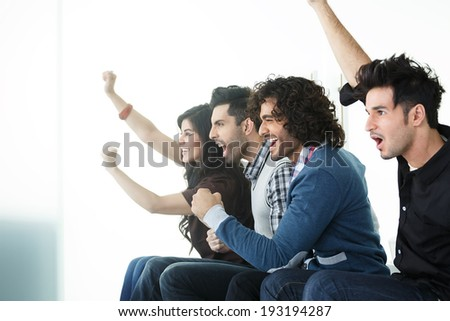 group of friends cheering while watching  imaginary television. - stock photo