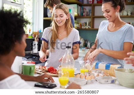 Group Of Friends Cooking Breakfast In Kitchen Together - stock photo