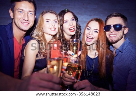 Group of friends drinking champagne and celebrating holiday - stock photo