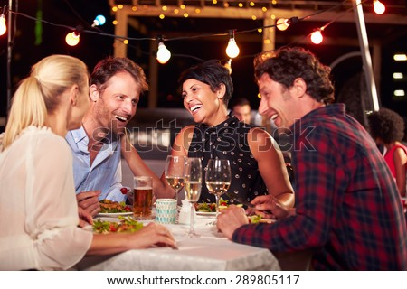 Group of friends eating dinner at rooftop restaurant - stock photo