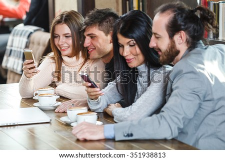 Group of friends ein cafe looking at smartphones - stock photo
