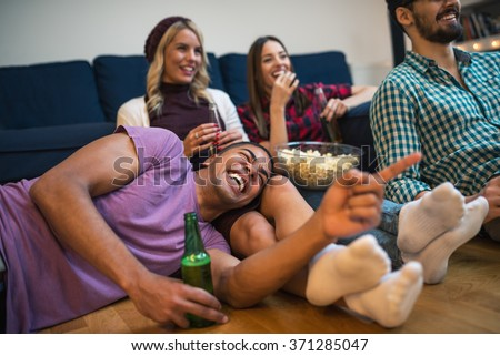 Group of friends enjoying a great movie with beer and popcorn. Focus on the smile. - stock photo