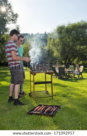 Group of friends enjoying a nice, warm, summer evening with food and drinks. Two men tending to a barbecue, with a group of their friends sitting around a picnic table in the background - stock photo