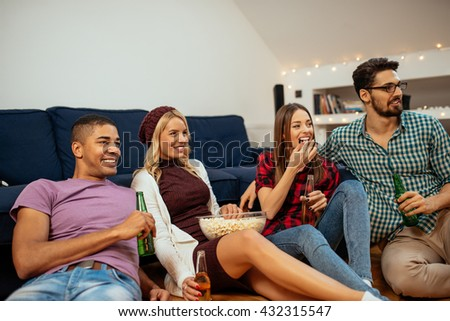 Group of friends enjoying beer and pop corn at home. - stock photo