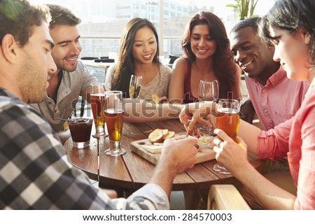Group Of Friends Enjoying Drink And Snack In Rooftop Bar - stock photo
