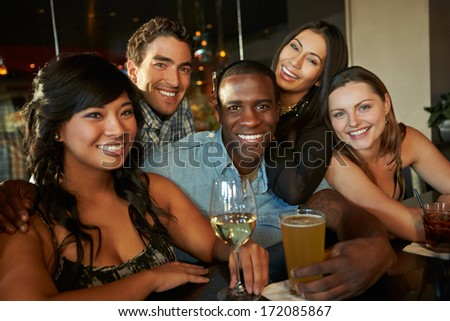 Group Of Friends Enjoying Drink At Bar Together - stock photo